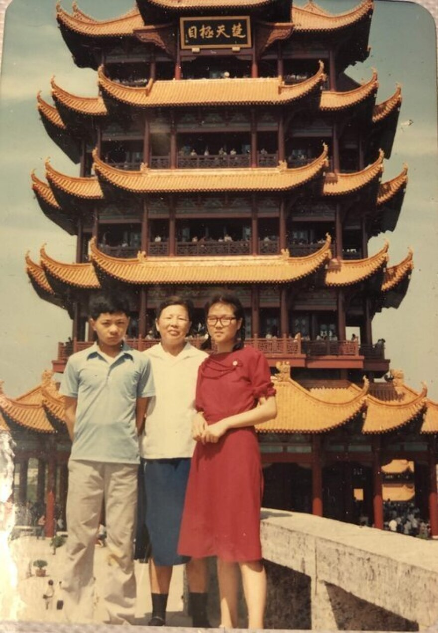 Laura Gao's mother (in the red dress) poses with her family in front of the Yellow Crane Tower in Wuhan before leaving for college in 1985. Gao visited that landmark for the first time 20 years later.