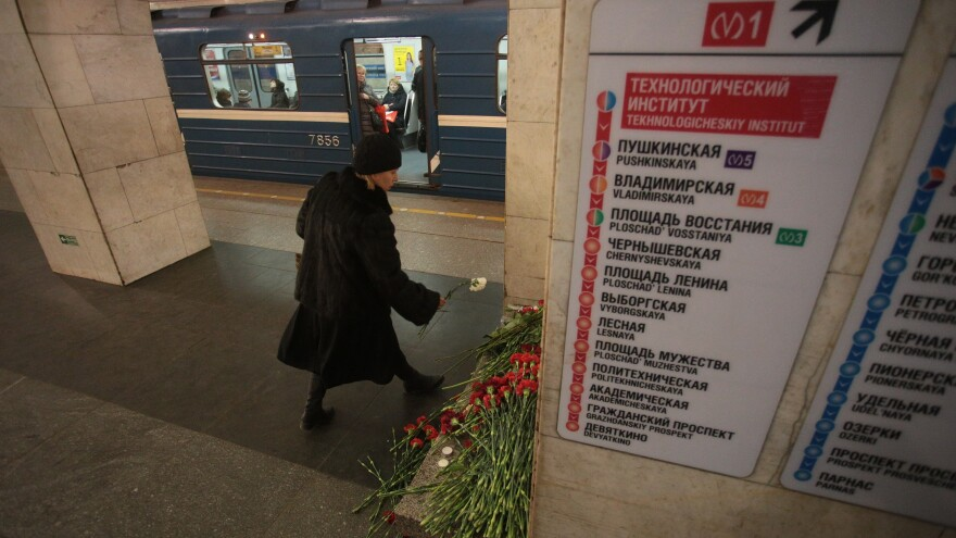 People lay flowers at the Technology Institute subway station in St. Petersburg, Russia, on Tuesday. Federal investigators say they found remains of a man they believe carried out Monday's attack in a subway train.