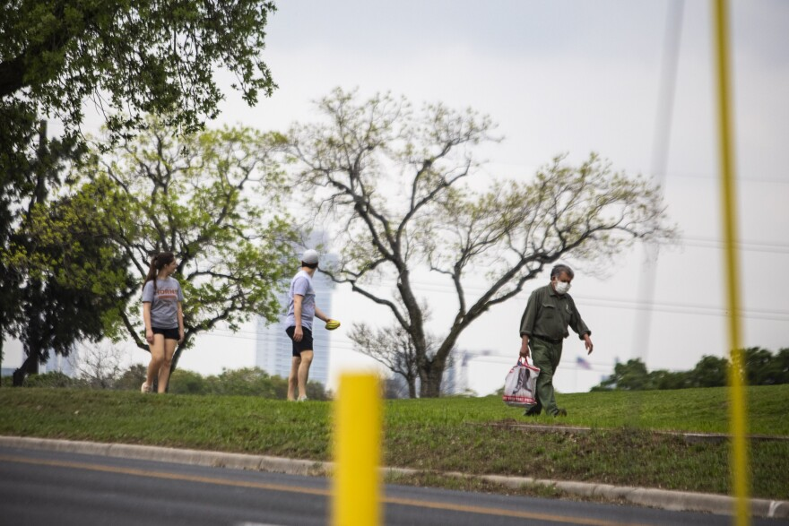 A man wearing a face mask walks in the Hancock neighborhood of Austin during the coronavirus pandemic.