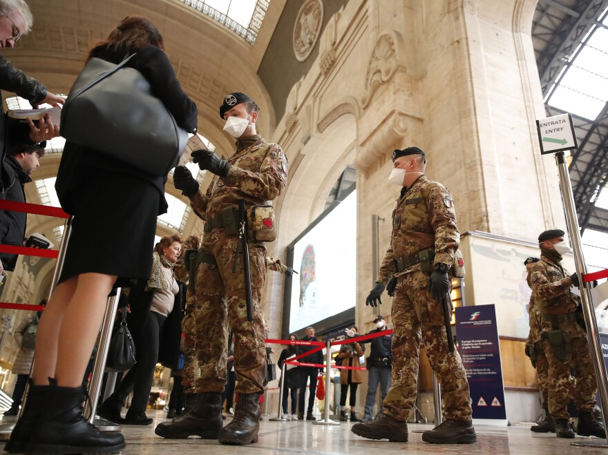 "Police officers and soldiers check passengers leaving the main train station in Milan, Italy. The government declared on Monday that the whole country is a ""red zone."""