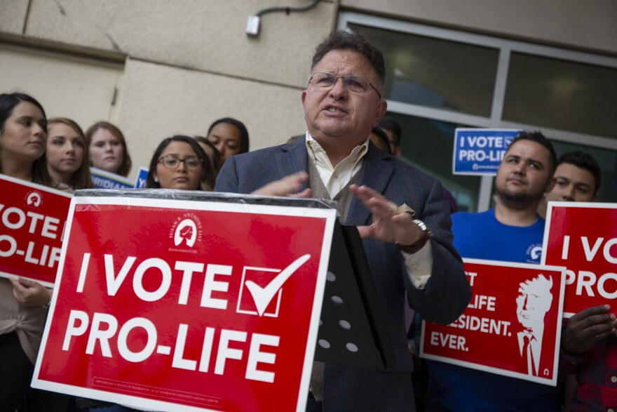 A man stands at a podium with a sign that says I vote pro life.