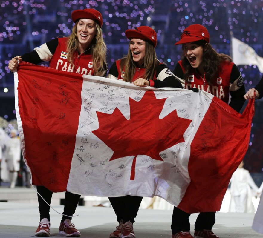Canadian athletes hold up the national flag during the 2014 Winter Olympics in Sochi, Russia. Sen. Ted Cruz was born in Calgary, and some question his eligibility to run for president in the U.S.