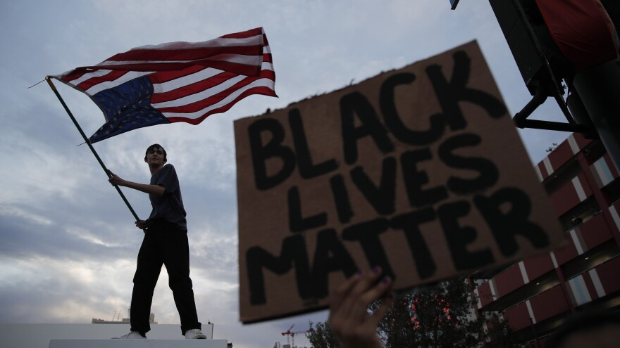 A man waves an upside-down American flag during a protest in Las Vegas following the death of George Floyd, a black man who died after a white Minneapolis police officer knelt on his neck.