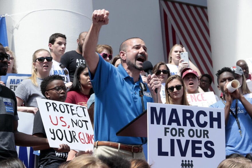 Leon Superintendent Rocky Hanna stands at a podium on the Florida Capitol steps with fist raised. He is flanked by protesters with signs protesting gun violence.