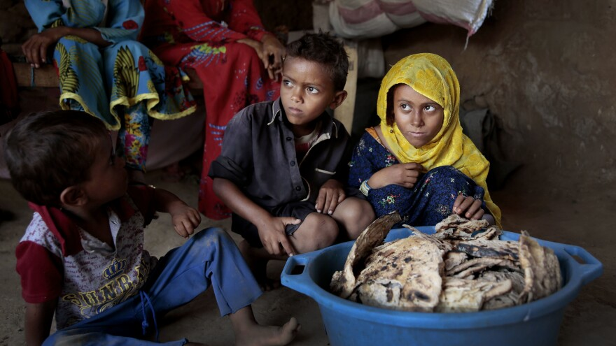 Children sit in front of a tub of moldy bread in their shelter in Aslam, Hajjah, Yemen, last month. The U.N. has estimated that up to 14 million Yemenis — about half the country's population — will suffer severe food shortages in the next few months.