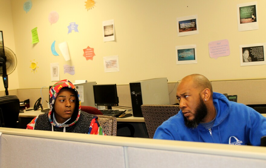 St. Louis Public Schools curriculum instructor Sylvester McClain, right, talks with student Jaevon Gill at Workforce High School.