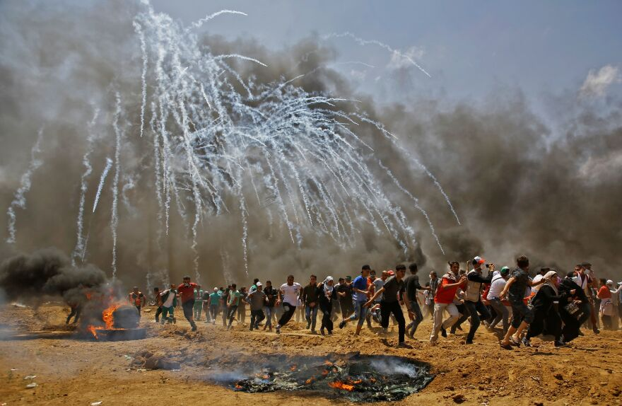 Palestinians run for cover from tear gas during clashes with Israeli security forces near the border between Israel and the Gaza Strip.