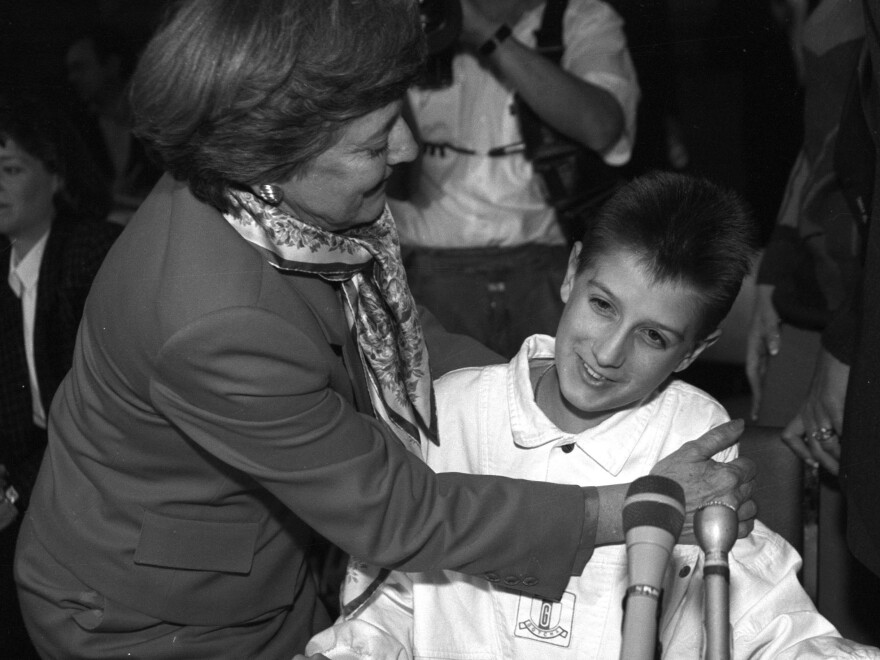 Ryan White gets a hug from Dr. Cory SerVaas after testifying to a presidential commission on AIDS in 1988. He told the panel of his battle with the disease and the taunts and jeers he endured from classmates.