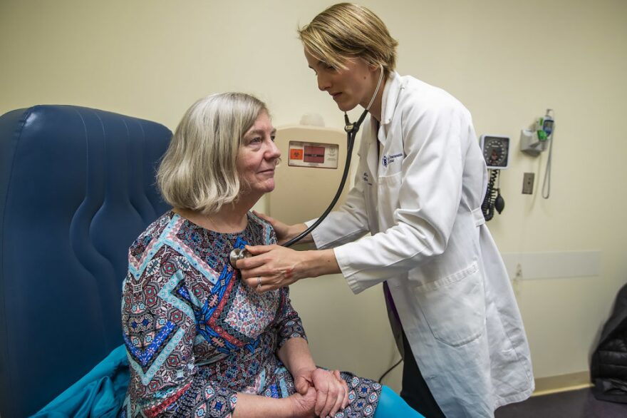Rice checks Mary Heafy's breathing during a checkup for her asthma at the Beth Israel Deaconess clinic. Climate change does seem to be extending the Boston region's ragweed season, Rice tells Heafy.