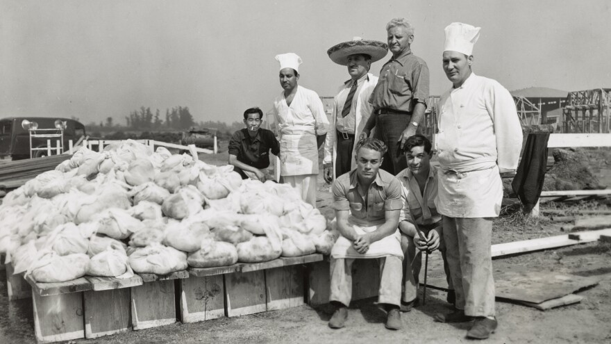 "Men pose with piles of wrapped beef, ready for the barbecue pits, at a Los Angeles sheriff's barbecue. The end goal of the America Eats project was to assemble material for a book exploring ""American cookery and the part it has played in national life, as exemplified in the group meals that preserve not only traditional dishes, but also transitional attitudes and customs."""