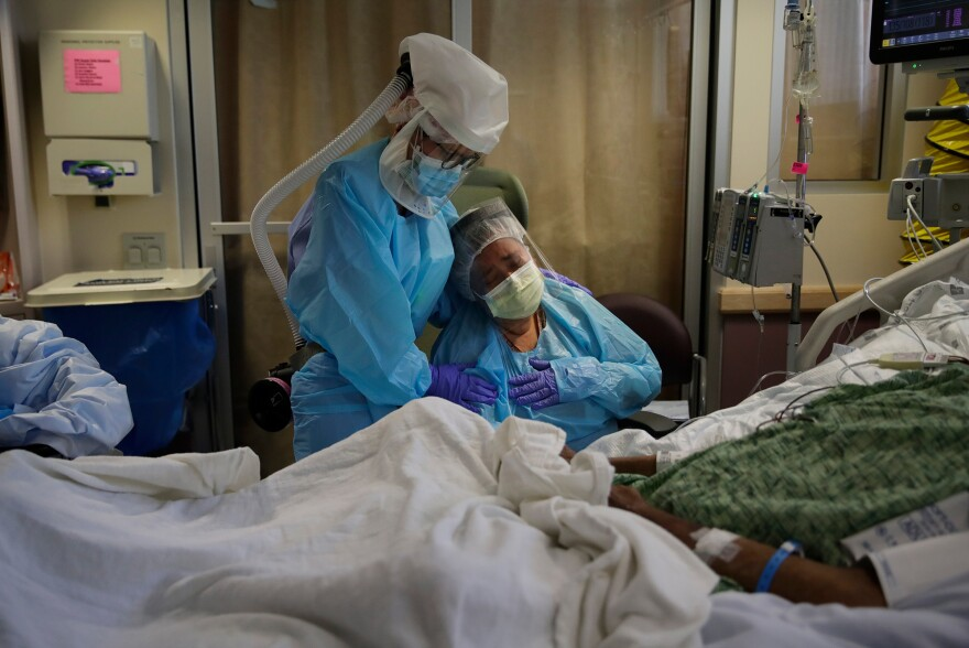 Nurse Michele Younkin (left). comforts Romelia Navarro as she sits at the bedside of her dying husband, Antonio Navarro, in St. Jude Medical Center's COVID-19 unit in Fullerton, Calif on July 31. Antonio was Younkin's first COVID-19 patient to pass on her watch.