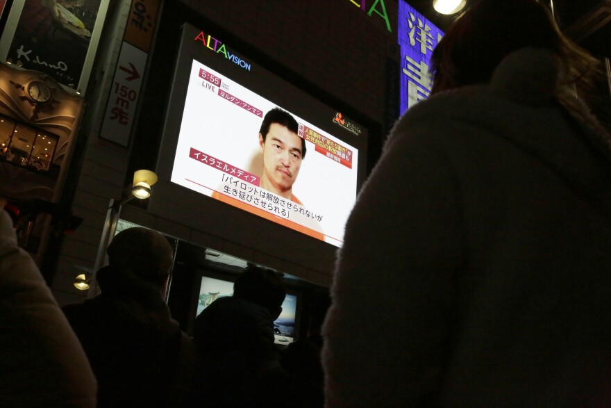Passersby watch a TV news program Wednesday in Tokyo reporting on a video posted on YouTube by extremists that purports to show Japanese hostage Kenji Goto.