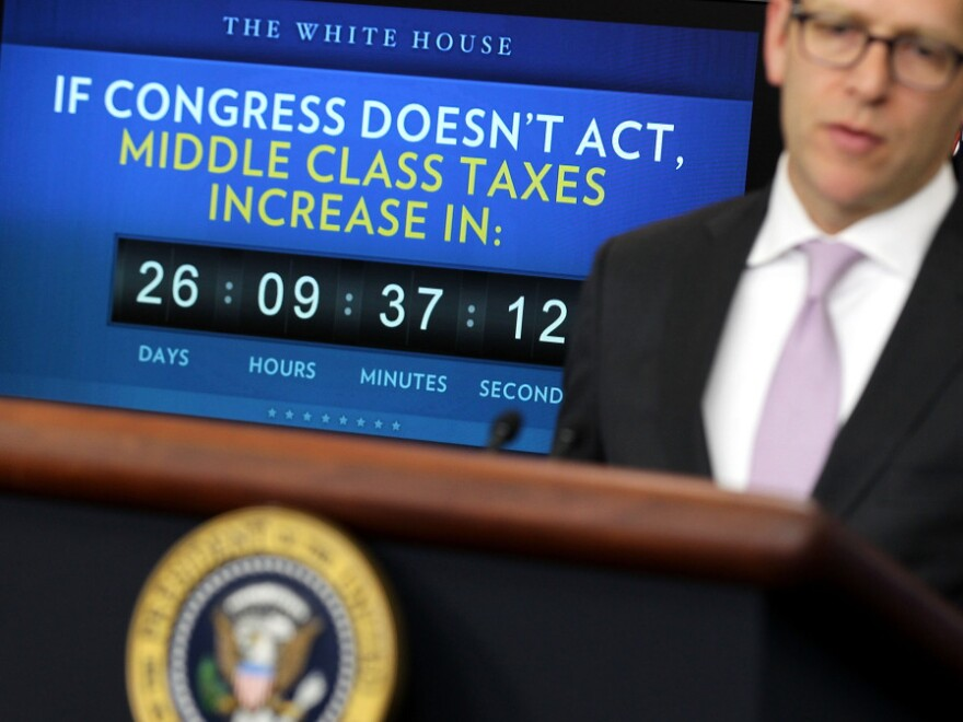 White House press secretary Jay Carney speaks Monday during his daily press briefing, as a clock counting down the expiration of the payroll tax cut benefit looms in the background.