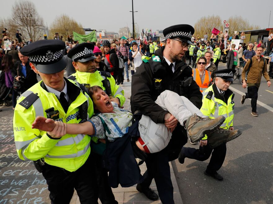 Police arrest a climate change activist near Waterloo Bridge in London on Wednesday. Authorities have made about 300 arrests since protests began Monday.