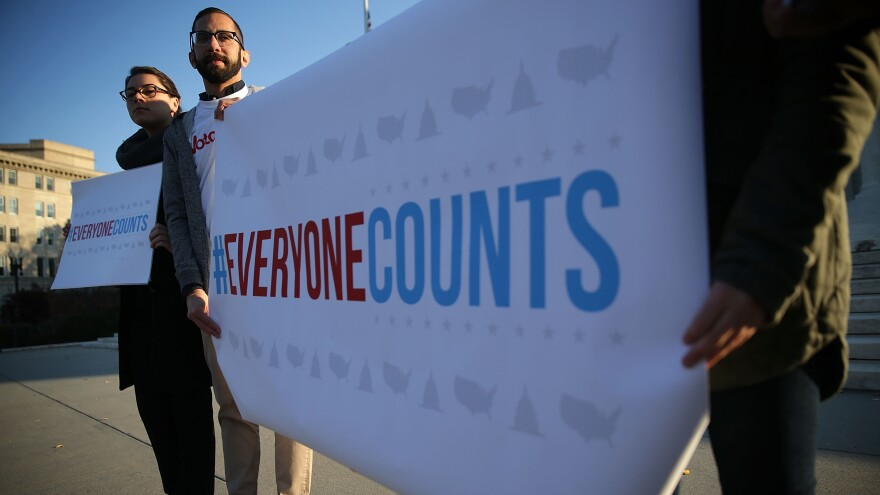 Activists hold signs during a news conference in front of the Supreme Court Tuesday.