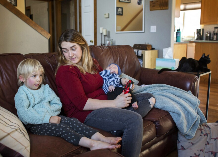 Amber Gorrow and her daughter, Eleanor, 3, pick out a show to watch after Eleanor's nap at their home in Vancouver, Wash., on Wednesday. Eleanor has gotten her first measles vaccine, but Gorrow's son, Leon, 8 weeks, is still too young to be immunized.