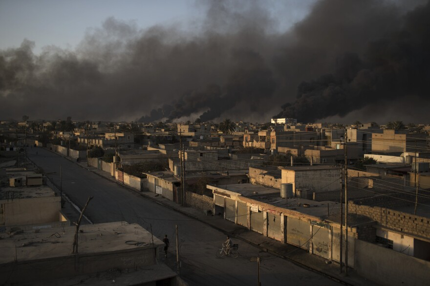 A man rides his bike on a street as smoke rises from burning oil fields on Monday in Qayara, south of Mosul, Iraq.