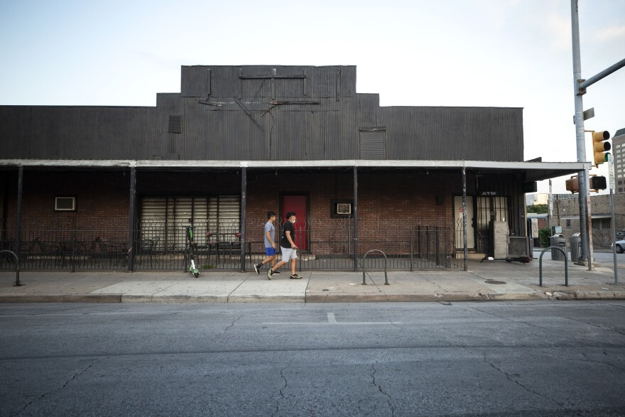 Pedestrians walk past closed music venues in the Red River Cultural District in September.