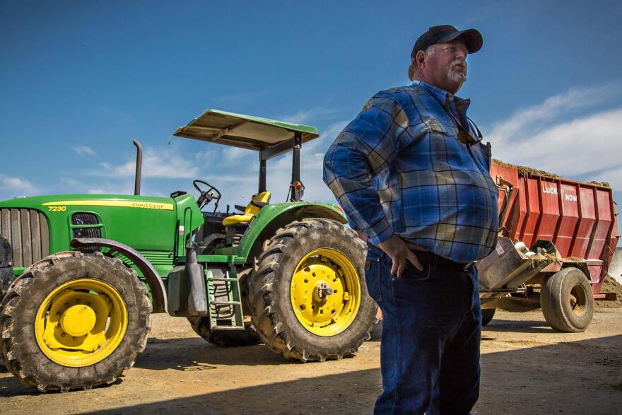 John Larson stands in front of a tractor