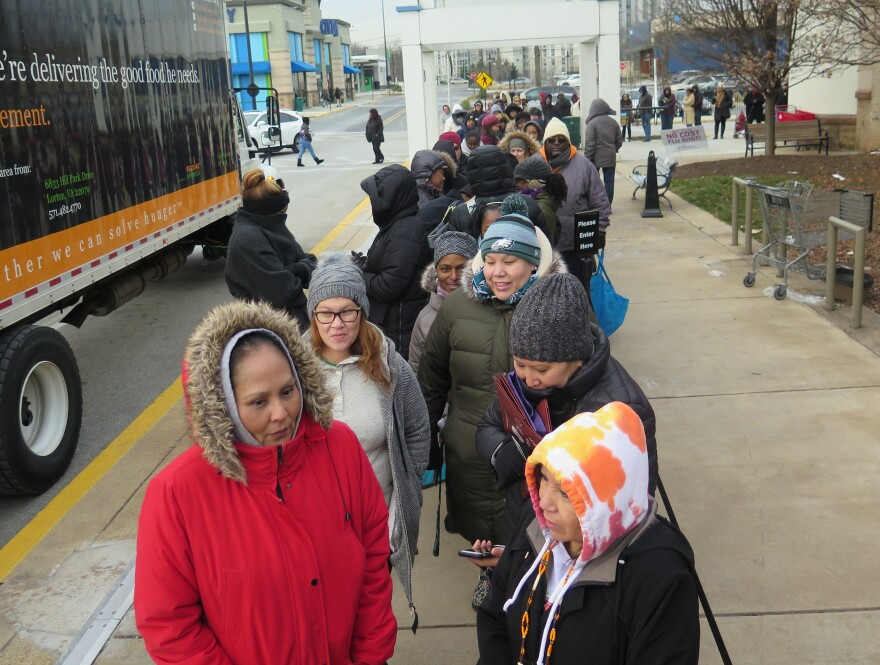 Federal workers wait for food distribution to begin on Saturday at a pop-up food bank in Rockville, Md. The Capital Area Food Bank is distributing free food to government employees during the government shutdown.