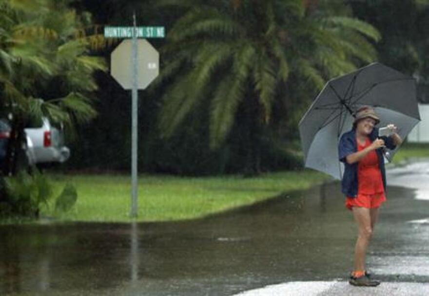 A woman takes a photo of flooded streets in the Shore Acres in St. Petersburg, Fla., Tuesday, June 7, 2016. Remnants of Tropical Storm Colin was continued to dump rain along Florida's gulf coast Tuesday.