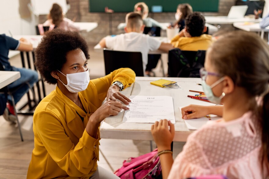 Black teacher with a face mask explaining exam results to elementary student in the classroom.