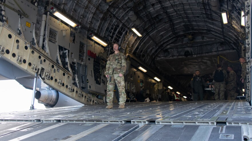 A National Guard member stands near an open airplane bay door
