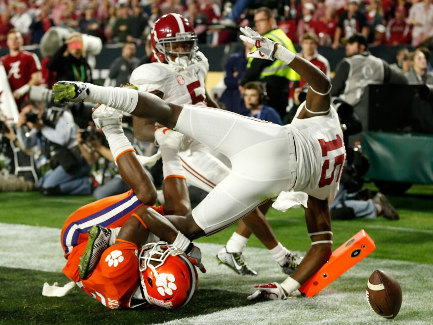Wide receiver Artavis Scott of the Clemson Tigers loses the ball in the end zone as he's bowled over by Ronnie Harrison of the Alabama Crimson Tide in the third quarter.