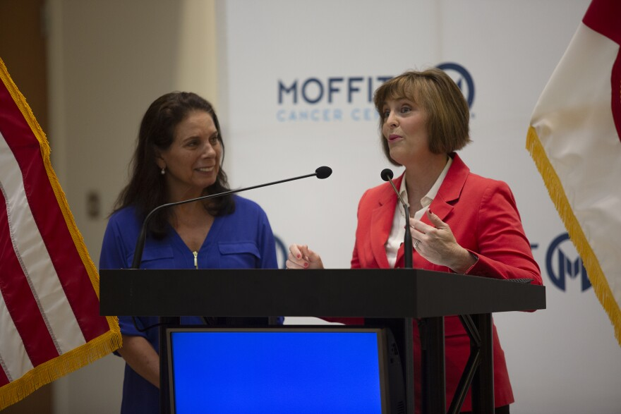 Dr. Anna Giuliano and U.S. Rep. Kathy Castor stand at a podium speaking to the press.