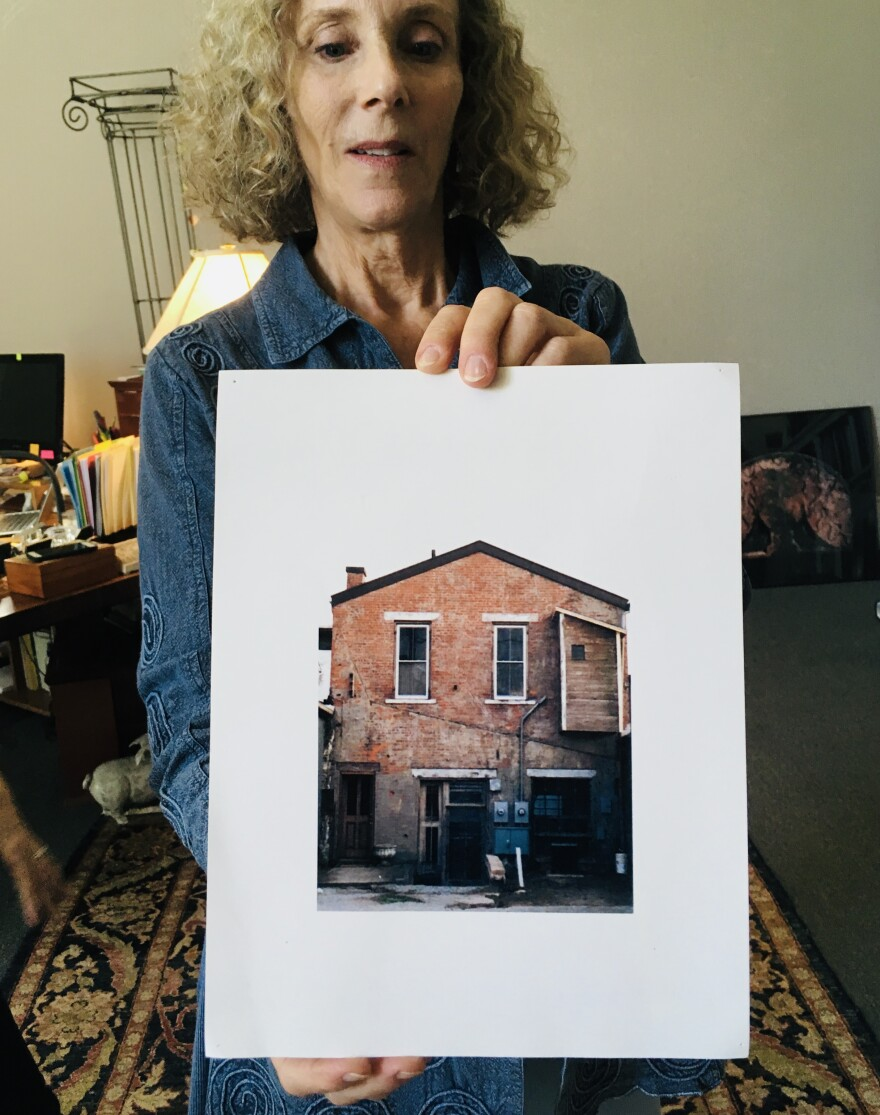 Orange Frazer Publisher Marcy Hawley holds up a photo of the press's offices before the mural.
