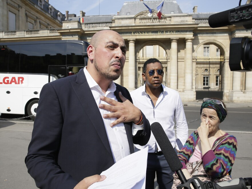 Marwan Muhammad (left) of the Collective Against the Islamophobia in France, one of the parties in a lawsuit against the town of Villeneuve-Loubet, speaks to the media following the ruling on a burkini ban.