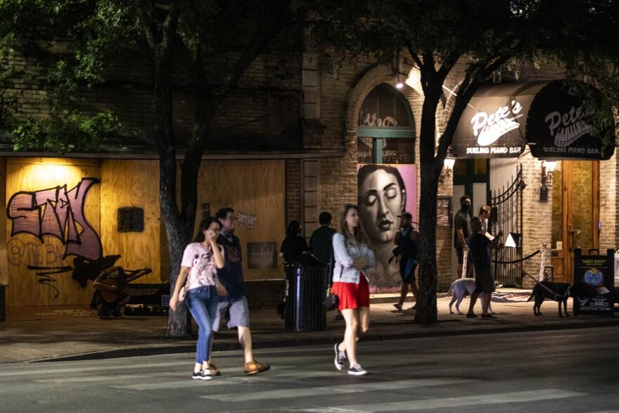 Pedestrians cross the street near bars on East Sixth Street in May.