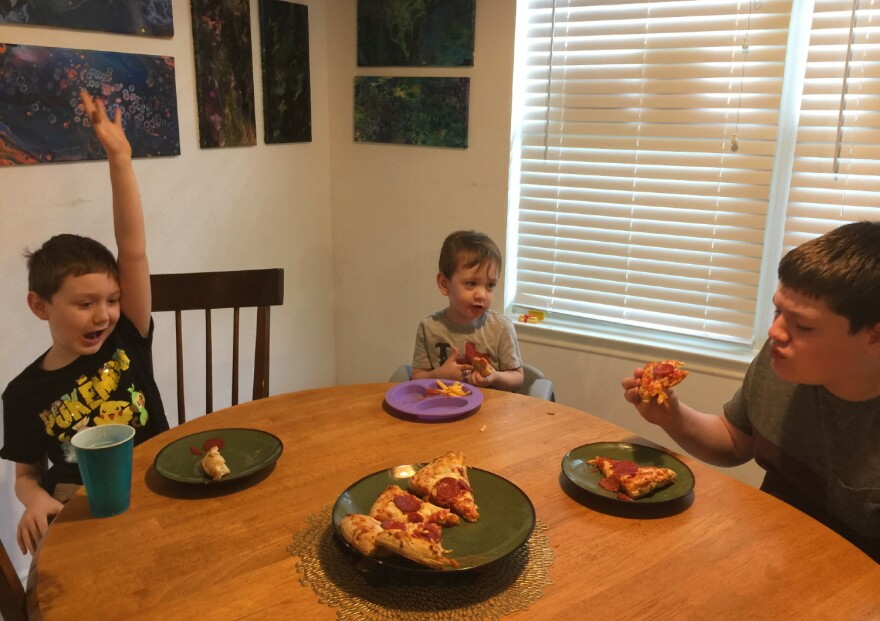 Tracy Sinha's sons Finnigin, Rama and Emerson eat pizza during a break from virtual learning on Sept. 3, 2020.