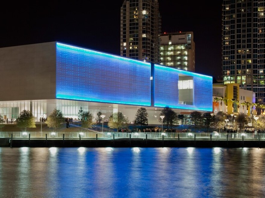 A wall of LED lights above the Tampa Museum of Art shine blue over downtown.