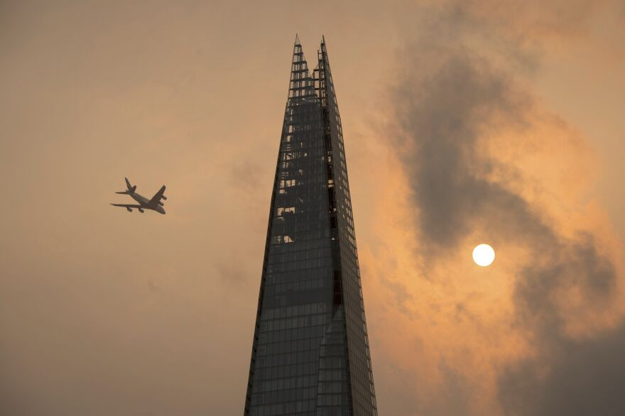 A plane flies past the Shard in central London on Monday amid skies that took on an unusual orange color caused by storm Ophelia.