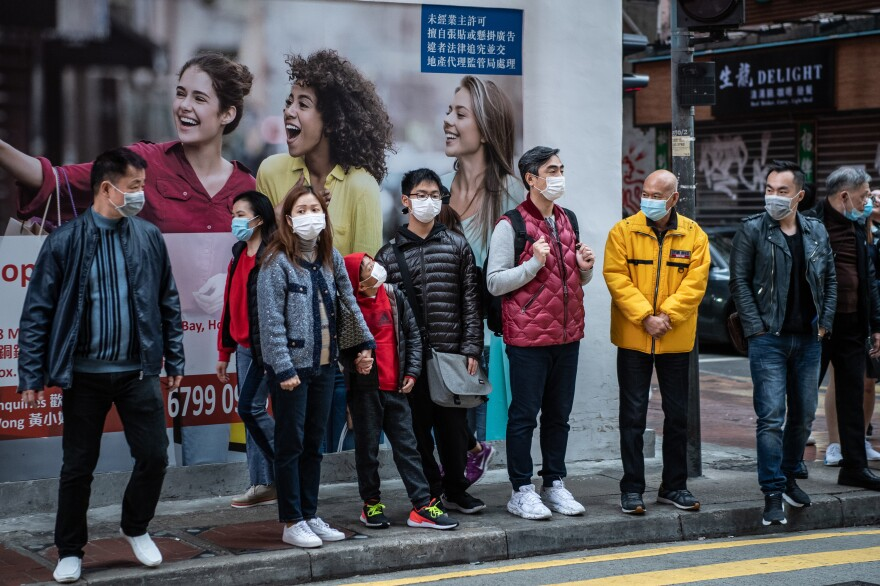 For societies that were affected by the SARS epidemic, the widespread usage of masks was more quickly adopted during the spread of COVID-19. Photograph of people waiting to cross the street in the Causeway Bay neighborhood of Hong Kong, Monday, January 27, 2020.