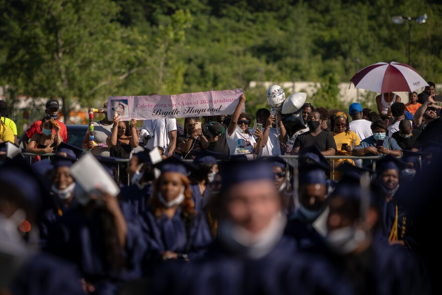 Families gathered around a fence separating them from students despite attempts for the graduation to be socially distanced.