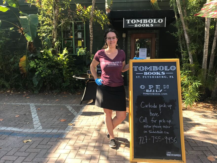 "Alsace Walentine, owner of Tombolo Books, stands outside of her store next to a sign that says ""Curbside pickup here!"""