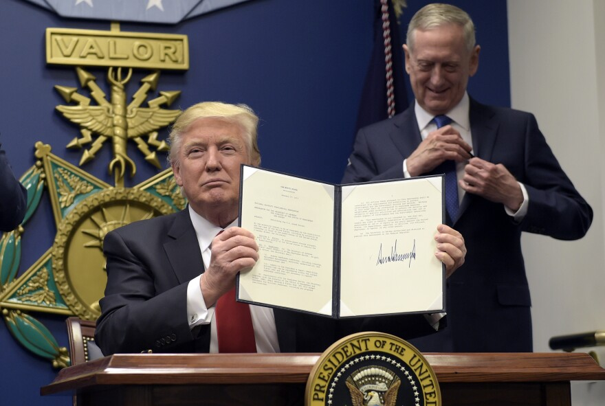 President Trump, with Defense Secretary James Mattis, shows his signature on an executive action to rebuild the military, during an event at the Pentagon on Friday.