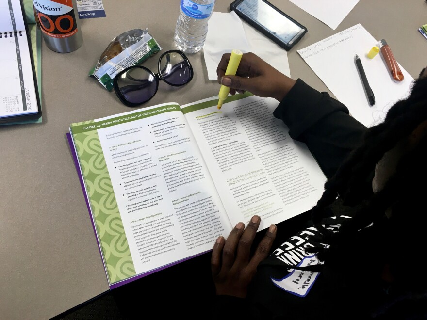 Participants use workbooks to learn the steps of mental health first aid at a recent training in St. Louis