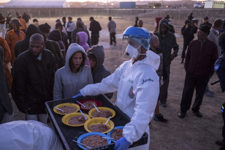 People receive food at a camp set up to house them during the coronavirus lockdown in Cape Town. Many are unhappy with the conditions of their confinement and worry that overcrowding poses a risk of catching the virus.