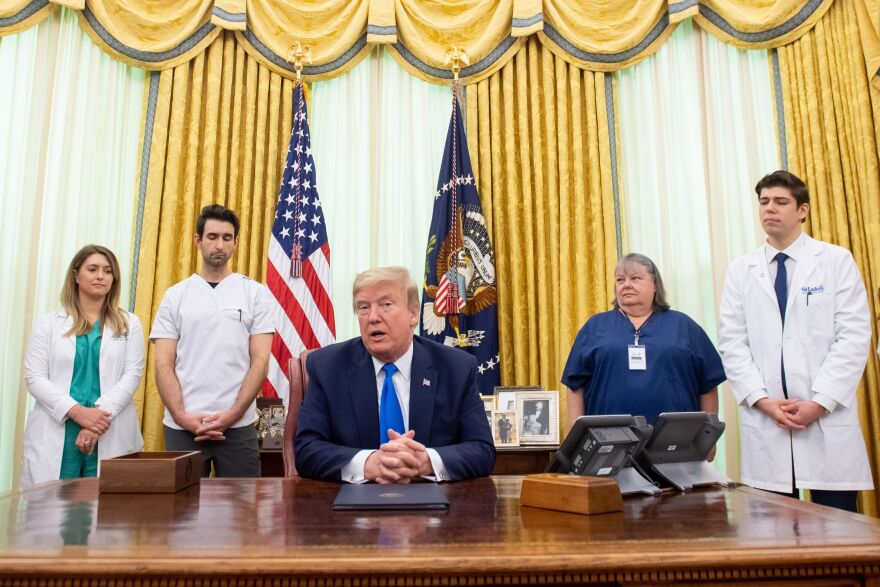 President Trump speaks about COVID-19 alongside nurses after signing a proclamation in honor of National Nurses Day in the Oval Office of the White House on Wednesday. Trump and Vice President Pence have not worn face masks during public events, which goes against the administration's recommendations.