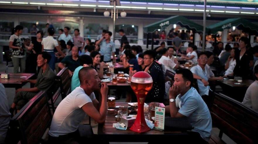 """North Koreans enjoy beer and snacks last August during the Taedonggang Beer Festival in Pyongyang. The festival, the first of its kind in the country, was held as a promotional event for the locally brewed beer. Korean signs in the background read """"Our country is the best."""""""