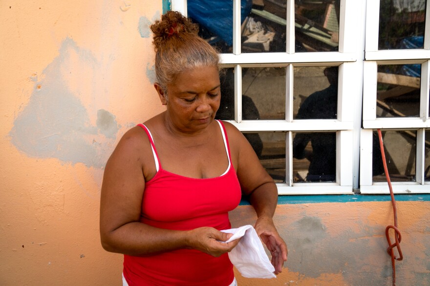 Ramos stands in the shade of her brother's house, where she and her husband have been living since Hurricane Maria hit last month.