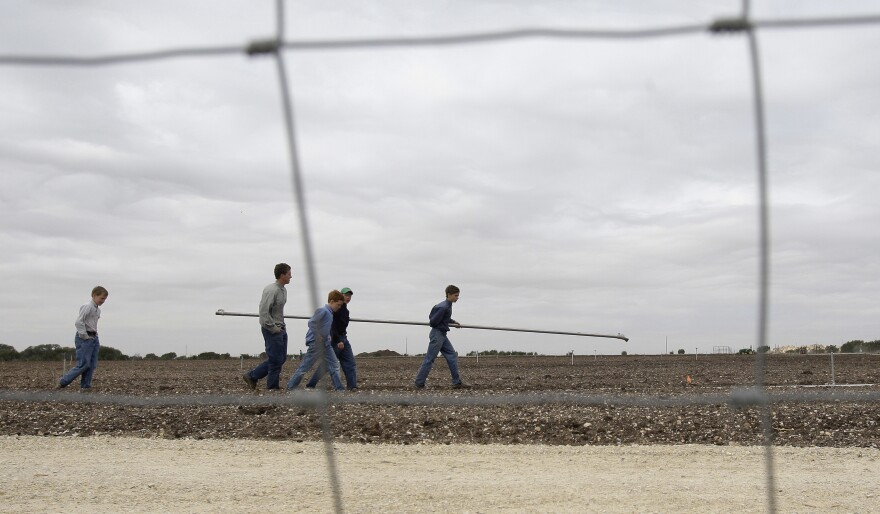 Boys walk through a potato field at the Yearning for Zion Ranch in Eldorado, Texas, in 2009.