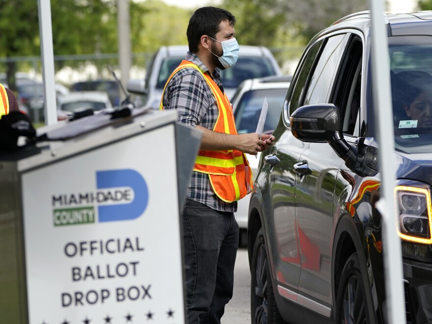 An election worker takes ballots from voters dropping them off at an official ballot drop box at the Miami-Dade County Board of Elections.