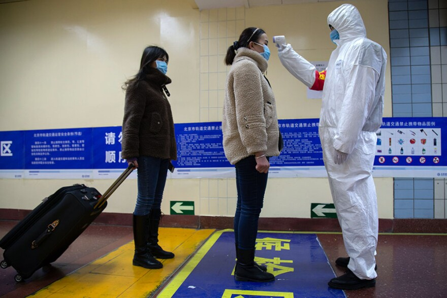 A health worker checks the temperature of women entering the subway on January 26, 2020 in Beijing, China.  (Betsy Joles/Getty Images)