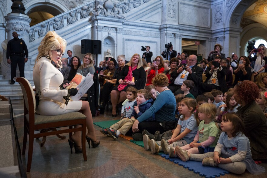 Dolly Parton reads <em>Coat of Many Colors</em>, a children's book based on one of her signature songs, to a group of children at the Great Hall of the Library of Congress in Washington, D.C., on Tuesday.