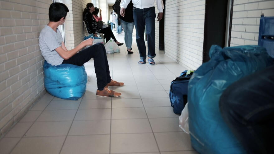 Migrants seeking asylum wait at the registration center on August 27, 2015 in Ingelheim, Germany. Germany is receiving more than 1,000 new migrants a day from countries like Syria, Eritrea and Afghanistan. In some cases, those migrants include unaccompanied minors, as NPR's Soraya Sarhaddi Nelson found at a similar center in Munich.