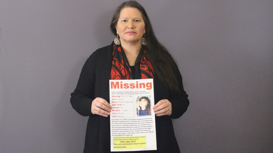 Carolyn DeFord poses with the missing persons poster for her mother, Leona Kinsey, who went missing in October 1999.
